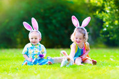 Children at Easter egg hunt. Two little children, cute curly toddler girl and funny baby boy wearing bunny ears having fun at Easter egg hunt playing with basket royalty free stock photos