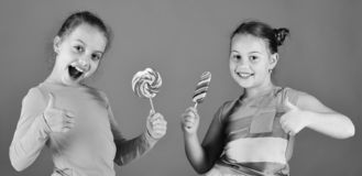 Children eat big colorful sweet caramels. Sisters with lollipops. Children eat big colorful sweet caramels. Sisters with round and long lollipops show thumbs up stock photos