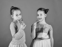 Children eat big colorful sweet caramels. Sisters with round, long shaped lollipops. Girls with happy faces. Children eat big colorful sweet caramels. Sisters stock images