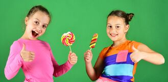 Free Children Eat Big Colorful Sweet Caramels. Sisters With Lollipops Royalty Free Stock Image - 187286186
