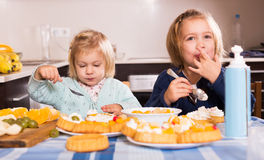 Children eat cakes at kitchen Stock Images