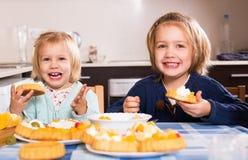 Children eat cakes at kitchen Stock Photos