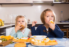 Children eat cakes at kitchen Royalty Free Stock Photo