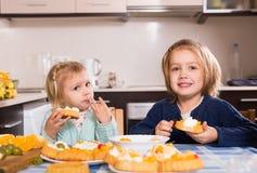 Children eat cakes at kitchen Royalty Free Stock Photos