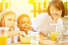 Children eat cereal at breakfast in summer camp. Happy kids eating breakfast cereal together at summer camp Royalty Free Stock Photos