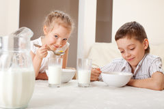Children eat cereals with milk royalty free stock image