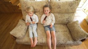 Children eat ice cream with chocolate on stick sitting on couch. Handheld shot. Children eating ice cream with chocolate on stick sitting on couch. Happy sister stock video footage