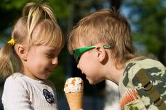 Children eat icecream. Small children in a summer garden eat cold icecream Royalty Free Stock Photo