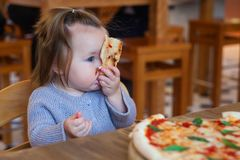 Children eat Italian pizza in the cafe. Adorable little girl eating pizza at a restaurant royalty free stock photography