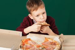 Children eat Italian pizza in the cafe. School boy is eating pizza for lunch. Child unhealthy meal concept. Hungry kids. Pizza re. Cipe. Kid eating pizza slice royalty free stock photos