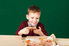 Children eat Italian pizza in the cafe. School boy is eating pizza for lunch. Child unhealthy meal concept. Hungry kids. Pizza re. Cipe. Kid eating pizza slice royalty free stock photo