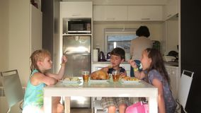 Children eat at the kitchen table served by mom. Woman in the background preparing dinner stock video