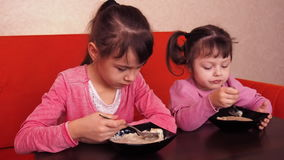 Children eat porridge. Two little girls eat porridge. Two sisters sitting on the orange couch and dinner. stock video footage