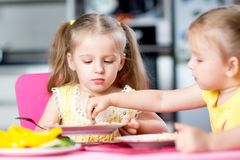 Children eat spaghetti with vegetables in nursery Royalty Free Stock Image
