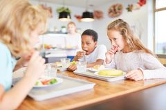 Children eat together in the canteen. Children as students eat lunch together in the canteen of the school stock photo