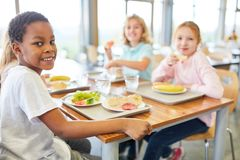 Children eat together in the canteen. Of the multicultural elementary school stock photo
