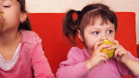 Children eating apples. Two sisters eating yellow apples while sitting on an orange couch. stock video