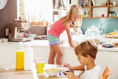 Children Eating Breakfast And Playing With Digital Tablet Stock Image