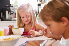 Children Eating Breakfast Whilst Playing With Mobile Phone Royalty Free Stock Photo