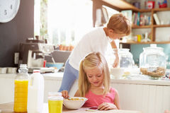 Children Eating Breakfast Whilst Playing With Mobile Phone Stock Photo