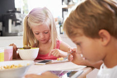 Children Eating Breakfast Whilst Playing With Mobile Phone Royalty Free Stock Image
