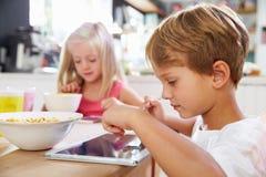 Children Eating Breakfast Whilst Using Digital Tablet Stock Image