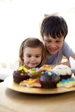 Children eating confectionery at home. Happy little girl and her brother eating confectionery at home Stock Images