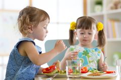 Children eating food in daycare centre Stock Photography