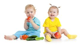 Children eating fruits and vegetables isolated. On white stock images