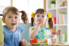 Children eating healthy food and cookie at kindergarten Royalty Free Stock Photo
