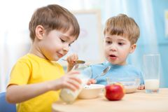 Children eating healthy food indoors Royalty Free Stock Photo