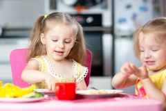 Children eating healthy food in nursery or at home. Cute children eat healthy food in nursery or at home stock photos