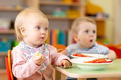 Children eating healthy food in nursery or kindergarten royalty free stock photos