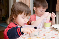 Children eating lunch at home, healthy food concept, kids enjoying bread and yogurt, sibling emotional faces, healthy breakfast Stock Photos