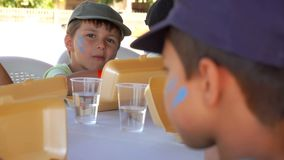 Children eating lunch from lunchboxes during break. Group of children eating lunch from lunchboxes during the break between games and activities at school. The stock video footage