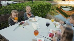 Children eating at the outdoor cafe stock video footage