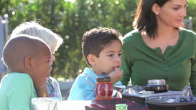 Children Eating Packed Lunch Outdoors With Teacher Royalty Free Stock Photo
