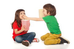 Children eating popcorn. Adorable boy and girl having great time eating popcorn, isolated on white Stock Images
