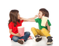 Children eating popcorn. Adorable boy and girl having great time eating popcorn, isolated on white Stock Image