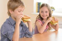Children eating sandwiches. Stock Photos