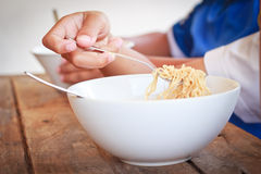Children eating their  instant noodle in white bowl. Stock Photo