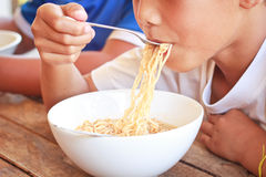 Children eating their  instant noodle in white bowl. Stock Photography