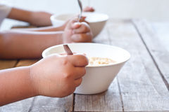 Children eating their  instant noodle in white bowl. Royalty Free Stock Photography