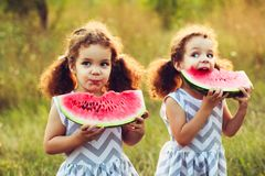 Children eating watermelon in the park. Kids eat fruit outdoors. Healthy snack for children. Little twins playing on the picnic bi. Child eating watermelon in Stock Images