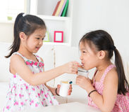 Children eating yoghurt. Eating yogurt. Happy Asian children eating yoghurt at home. Beautiful sisters . Healthcare concept Royalty Free Stock Image