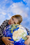 Children and ecology. A smiling girl keeping in a cute gesture a ball in form of Earth like a concept for ecology, environment and future, over blue sky Royalty Free Stock Photos