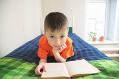 Children education, boy reading book lying on bed, child portrait smiling with book, educational interesting storybook Royalty Free Stock Images