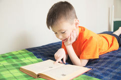 Children education, boy reading book lying on bed, child portrait smiling with book, interesting storybook Royalty Free Stock Photography