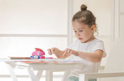 Children education concept. Beautiful little girl sticking pieces of paper on the art lesson class. Kids crafts. Learn Study Education School Knowledge Concept Royalty Free Stock Photo
