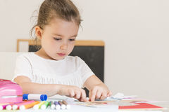 Children education concept. Beautiful little girl sticking pieces of paper mosaic on the art lesson class. Children education concept. Kids crafts. Learn Study Royalty Free Stock Photography